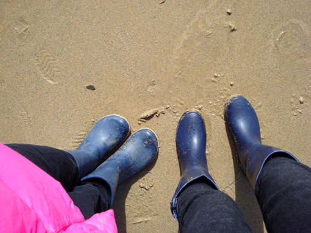 legs of a little girl and a young woman standing on wet beach sand in blue boots