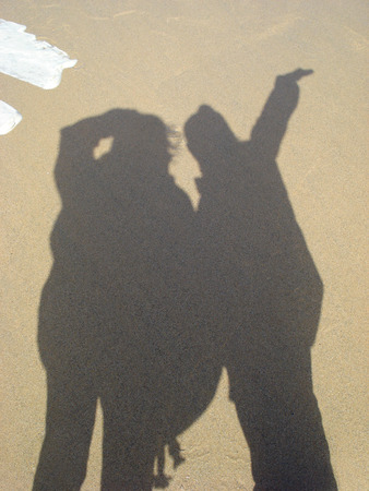 shadow of a little girl and a young woman standing on a beach