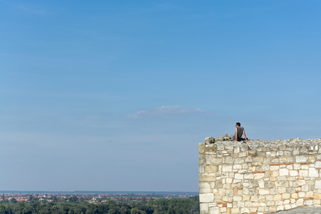 Dark haired young man with sunglasses and ear pods overseeing the cityscape on a bright summer day from the stone watchtower of Kalemegdan fort in Belgrade, Serbia