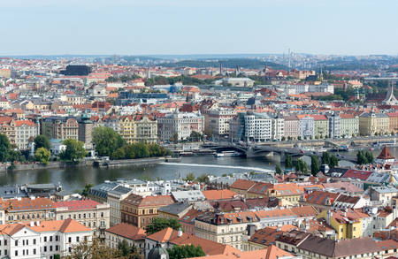 Prague panorama with colorful rooftops, row of Vltava river waterfront buildings and Dancing house in view