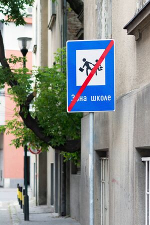 "Blue, red and white street traffic sign, showing a crossed out running boy and girl icons, with Cyrillic Serbian alphabet text saying: ""School zone�, on a gray daytime city street"