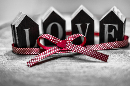 Black and white photo with a focus on red color as a symbol of love. Valentine's day greeting card with place for text.