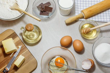 Ingredients for baking cakes. Eggs, flour, butter, oil, milk, honey, sugar and chocolate on light background. Baking concept, view from high angle.