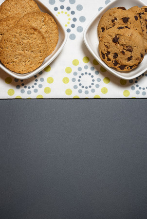 Two different kind of cookies, oatmeal and chocolate chip cookies in the white bowls. Top view flat lay background with space for text.