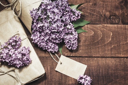 Close-up view of gift and bouquet of lilacs wrapped in kraft paper on a wooden background. Vintage toned photo.