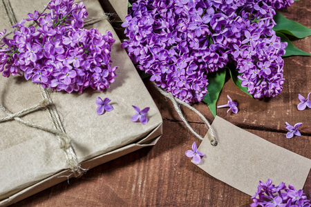 Close-up view of gift and bouquet of lilacs wrapped in kraft paper on a wooden background.