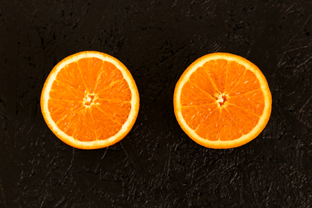 Close-up photo of two slices of orange on a black background. Top view with copy space. Reklamní fotografie