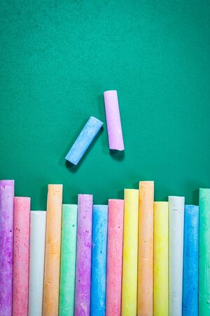 Multicolored chalks on a green chalkboard, back to school concept.