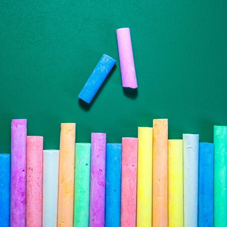 Square photo of multicolored chalks on a green chalkboard, back to school concept.