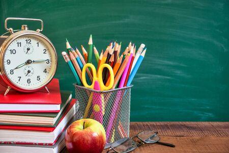 학교 칠판 앞 나무 탁자에 있는 학용품, 알람 시계, 사과, 책. 학교 개념으로 돌아가기. 스톡 콘텐츠