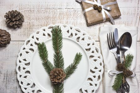 Festive table setting with vintage dishware, silverware, pine cone and branches decorations and gift box on rustic wooden table. Flat lay, top view, copy space. 写真素材