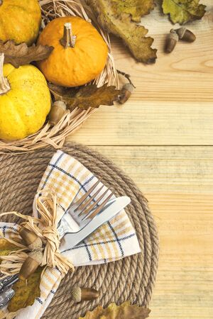 Rustic table setting for Thanksgiving diner with autumn leaves, acorns and pumpkins for decoration. Top view with copy space.