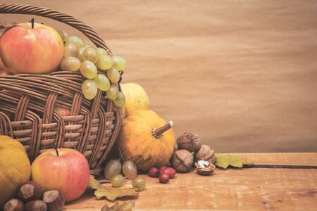 Autumn still life with fruits, pumpkins, rose hips and nuts on wooden table, copy space. Vintage toned photo. Stock Photo