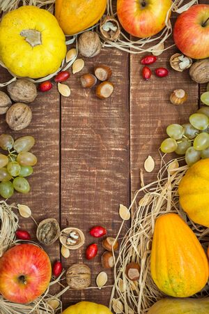 Autumn frame with fruits, pumpkins and nuts on rustic wooden background, top view with copy space. Autumn concept background.