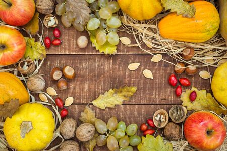 Autumn frame with fruits, pumpkins and nuts on rustic wooden background, top view with copy space. Autumn concept background. Stock Photo - 133301263