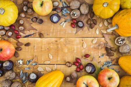 Autumn frame with fruits, pumpkins and nuts on rustic wooden background, top view with copy space. Autumn concept background. Standard-Bild - 133178961