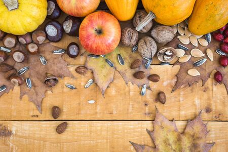 Autumn frame with fruits, pumpkins and nuts on rustic wooden background, top view with copy space. Autumn concept background. Standard-Bild - 133179167