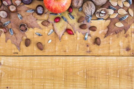 Autumn frame with fruits, nuts, seeds and leaves on rustic wooden background, top view with copy space. Autumn concept background. Stock Photo