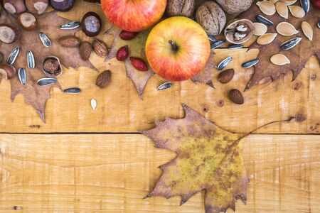 Autumn frame with fruits, nuts, seeds and leaves on rustic wooden background, top view with copy space. Autumn concept background. Standard-Bild - 133178306