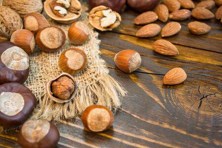 Mischung aus verschiedenen Nüssen auf rustikalem Hintergrund. Nahaufnahmefoto mit Kopienraum. Gesundes Ernährungskonzept.