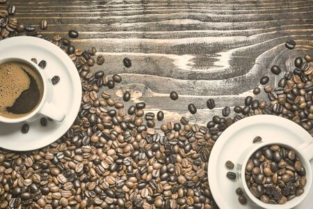 Coffee cups with black coffee and roasted coffee beans on rustic wooden background. Vintage toned photo. Top view, space for text. 版權商用圖片
