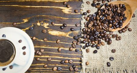 Black coffee in white cup and roasted coffee beans in wooden spoon on rustic background. Top view, space for text.