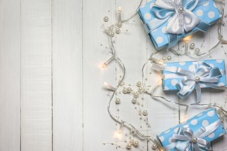 Top view of blue gift boxes with white and blue ribbon and lights decorated with pearls on white wooden background with copy space. Vintage toned photo. Christmas and New Year concept. Stock Photo