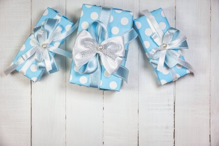 Top view of blue gift boxes with white and blue ribbon on white wooden background with copy space. Vintage toned photo. Christmas, birthday and New Year concept.