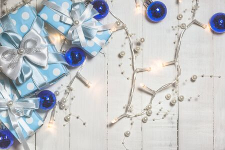 Top view of blue gift boxes with white and blue ribbon and christmas ornaments on white wooden background with copy space. Vintage toned photo. Christmas and New Year concept. Stock Photo