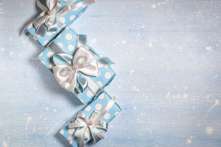Top view of blue gift boxes with white and blue ribbon on light blue textured background with copy space. Vintage toned photo. Christmas, birthday and New Year concept. Stock Photo