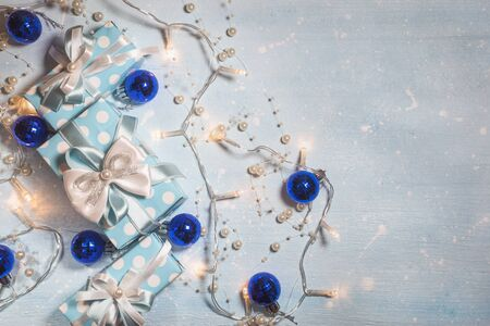 Top view of blue gift boxes with white and blue ribbon and christmas ornaments on light blue textured background with copy space. Vintage toned photo. Christmas and New Year concept.