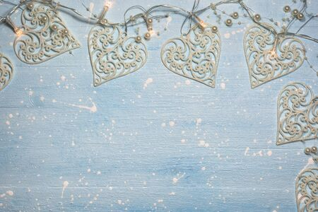 Christmas or winter composition. Pattern made of ornaments in heart shape and lights decorated with pearls on textured light blue background. Christmas, winter, new year concept. Flat lay, top view, copy space. Stock Photo