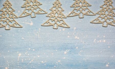 Christmas or winter composition. Pattern made of ornaments in the shape of tree on textured light blue background. Christmas, winter, new year concept. Flat lay, top view, copy space.