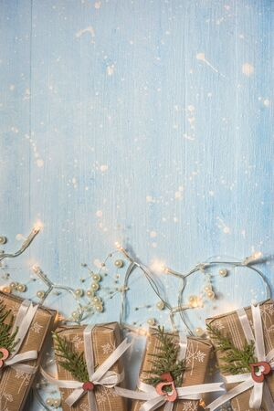 Christmas gift boxes and lights decorated with pearls on textured light blue background. Holiday and celebration concept for postcard or invitation. Top view with copy space.