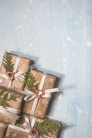 Christmas gifts wrapped in craft paper on textured light blue background. Holiday and celebration concept for postcard or invitation. Top view with copy space. Stock Photo
