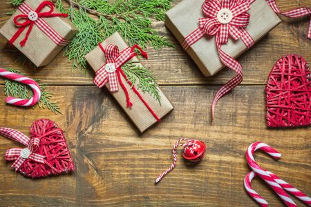 Christmas composition with handmade gift boxes wrapped in craft paper, branches, decorations and candy canes on rustic wooden table. Christmas or New Year greeting card with copy space, top view.