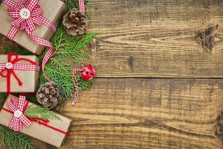 Christmas composition with handmade gift boxes wrapped in craft paper, branches and decorations on rustic wooden table. Christmas or New Year greeting card with copy space, top view.
