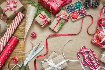 Christmas background with gift boxes, ribbons, paper rolls, decorations and candy canes on wooden table. Preparation for holidays. Top view with copy space.