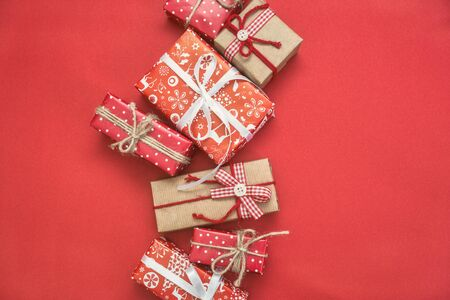 Christmas greeting card with different gift boxes on red background. Top view with copy space. Stock Photo