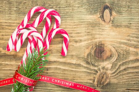 Candy canes wrapped with red Christmas ribbon on wooden background. Vintage toned photo. Top view with copy space on right side. Stock Photo