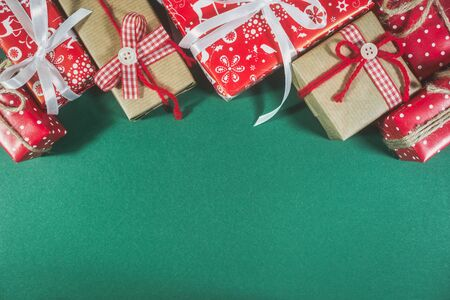 Christmas greeting card with different gift boxes on green background. Top view with copy space. Stock Photo