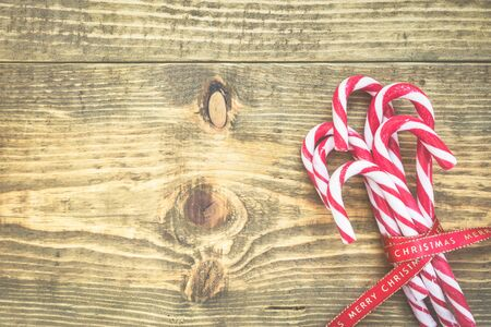 Candy canes wrapped with red Christmas ribbon on wooden background. Vintage toned photo. Top view with copy space on left side.
