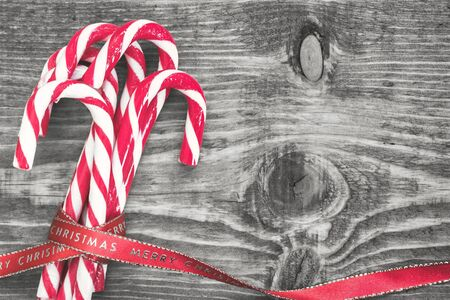 Candy canes wrapped with red Christmas ribbon on black and white background. Top view with copy space on right side.