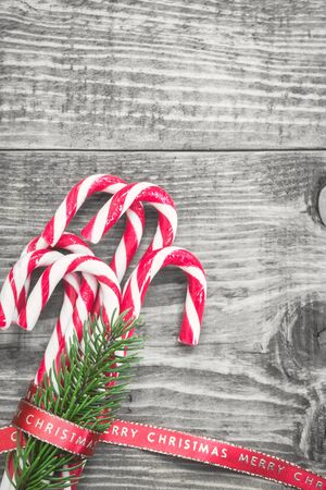 Candy canes wrapped with red Christmas ribbon on black and white background. Top view with copy space. Stock Photo