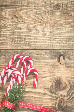 Candy canes wrapped with red Christmas ribbon on wooden background. Vintage toned photo. Top view with copy space.