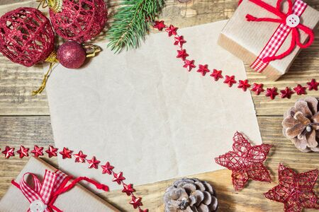 Blank paper with Christmas decoration, gifts and fir branches on wooden background. Top view with copy space. Stock Photo
