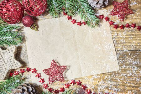 Blank paper with Christmas decoration, gifts, fir branches and snow on wooden background. Top view with copy space. Stock Photo