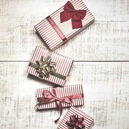 Christmas greeting card with different gift boxes on white wooden background. Top view with copy space. Vintage toned photo. Stock Photo