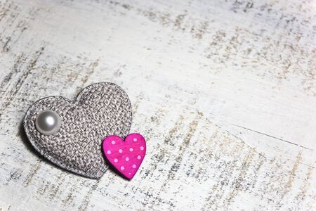 Fabric and wooden hearts on rustic white background. Valentines day concept. Empty space for text on right side.