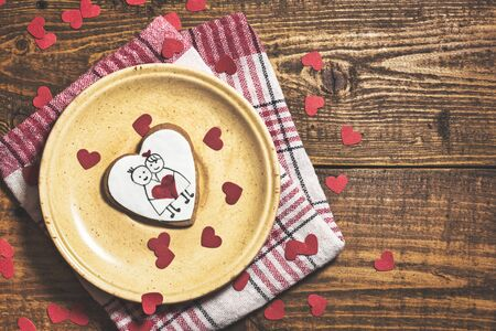 Heart shaped cookie for valentine's day on rustic wooden background. Top view with copy space.